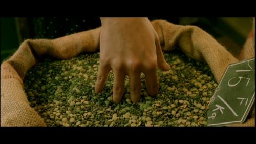Amélie com a mão no saco de  grãos