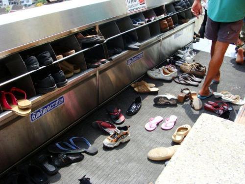 Calçados na entrada de um templo em Bangkok, maioria de chinelos