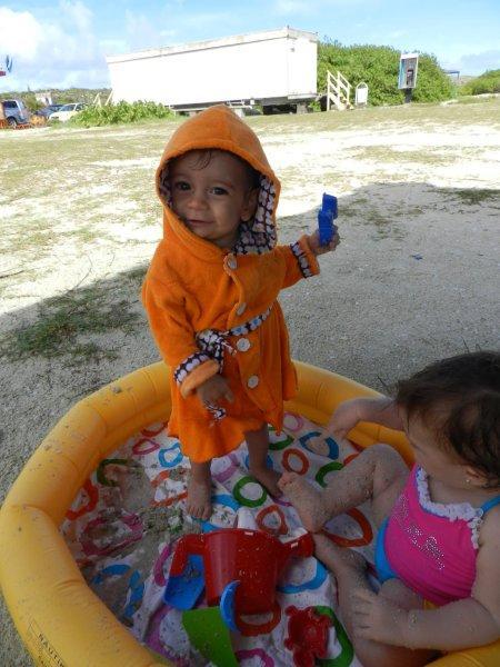 Amélie usando a banheira de viagem como piscina na praia