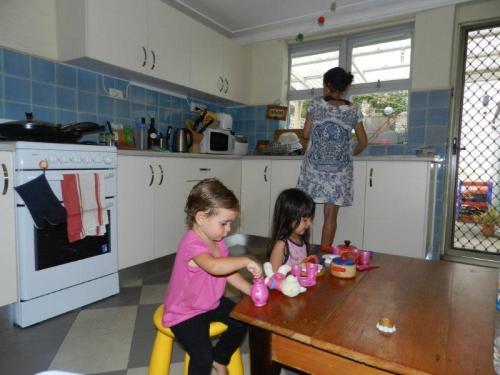 Eu e minha amiga Casandra brincando de fazer comidinha enquanto minha lava a louça