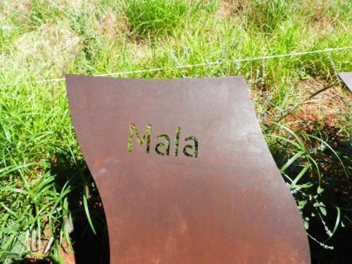 Placas em metal ao redor do Uluru que contam a lenda Mala