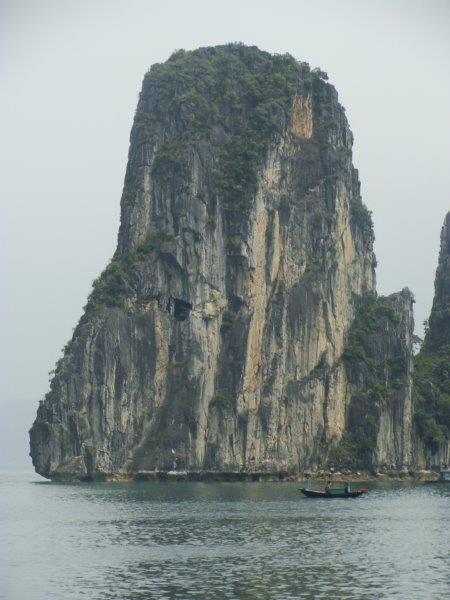 O barco quase desaparece perto da rocha