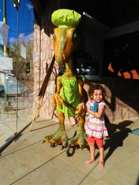 Amélie se divertindo com seu amigo dinossauro