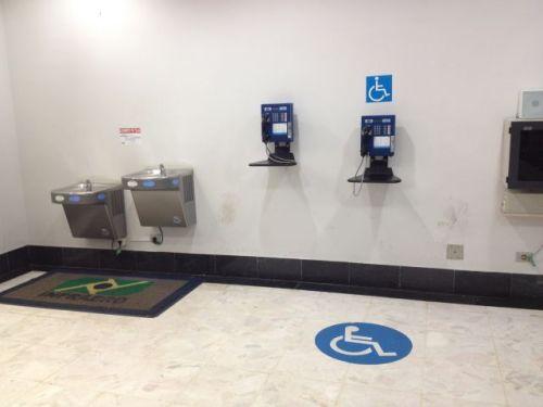 Telefone público e bebedouro acessíveis no aeroporto de Campo Grande
