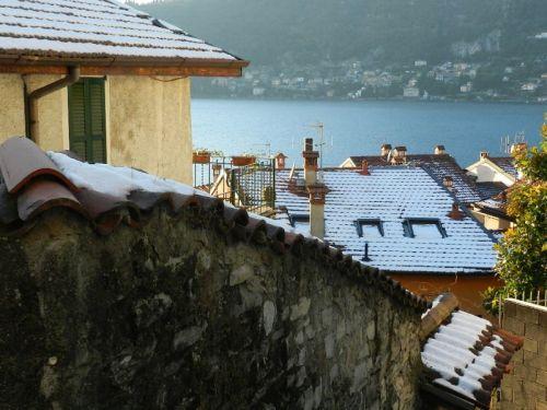 Telhados tomados pela neve e Lago Como ao fundo
